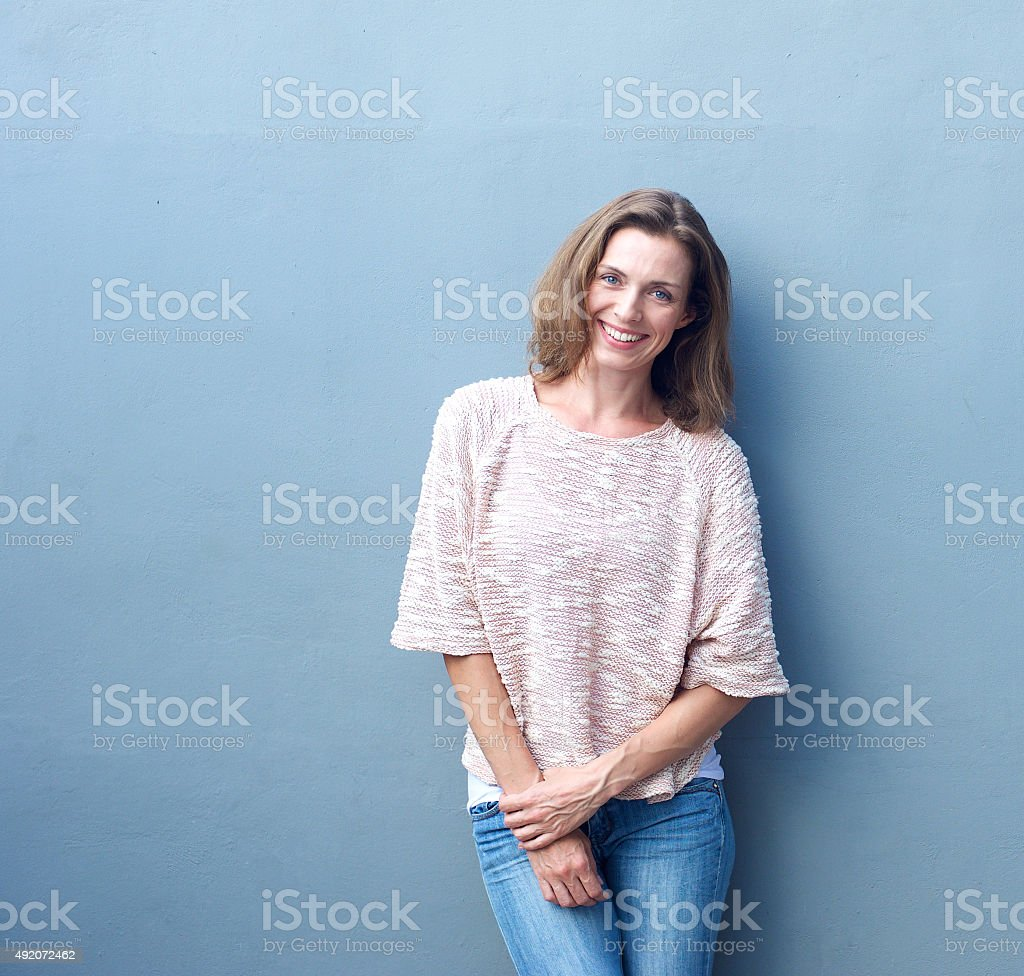 Attractive mid adult woman smiling on gray background stock photo