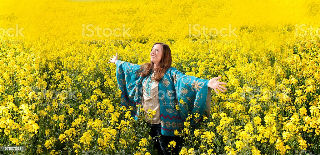 Attractive middle age woman with arms outstretched stock photo