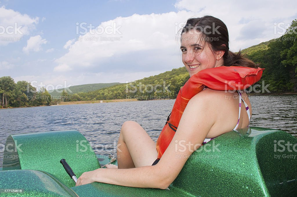 Attractive middle aged woman in paddle boat with life vest stock photo