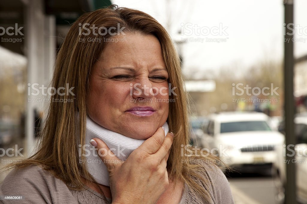 Attractive middle aged woman in pain and clutching neck brace stock photo