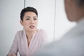 Attractive mixed race young businesswomen listening in meeting