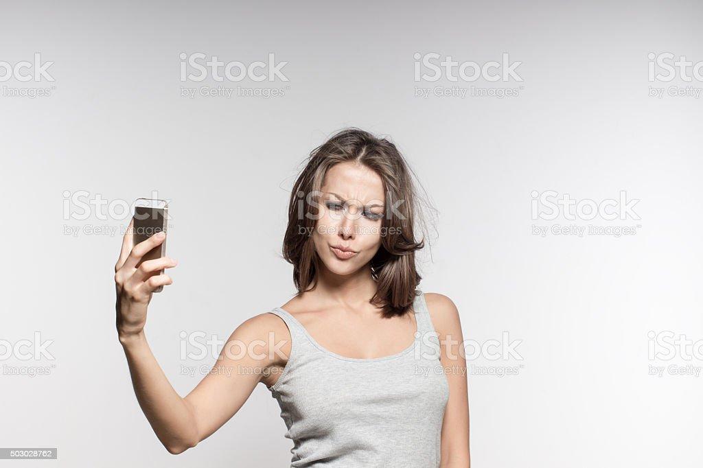 attractive model grimacing in studio, making selfies on phone camera stock photo