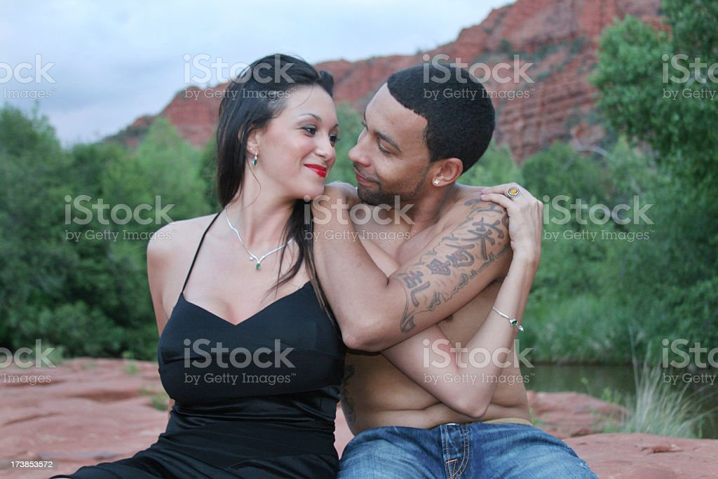 Attractive Multi-ethnic couple looking into each others eyes stock photo