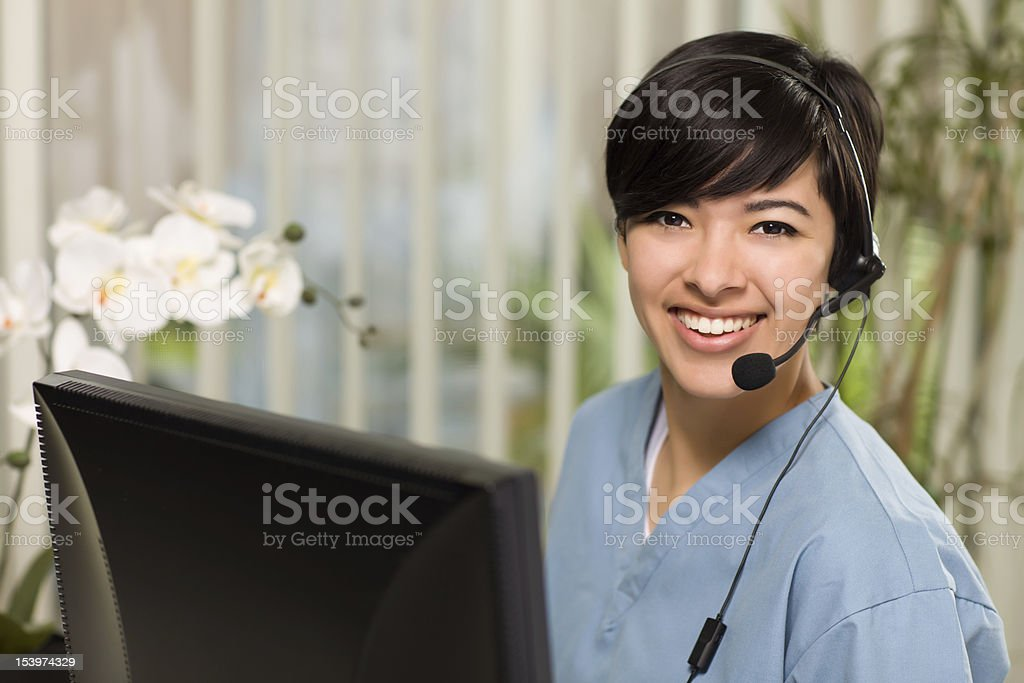 Attractive Multi-ethnic Young Woman Wearing Headset and Scrubs stock photo