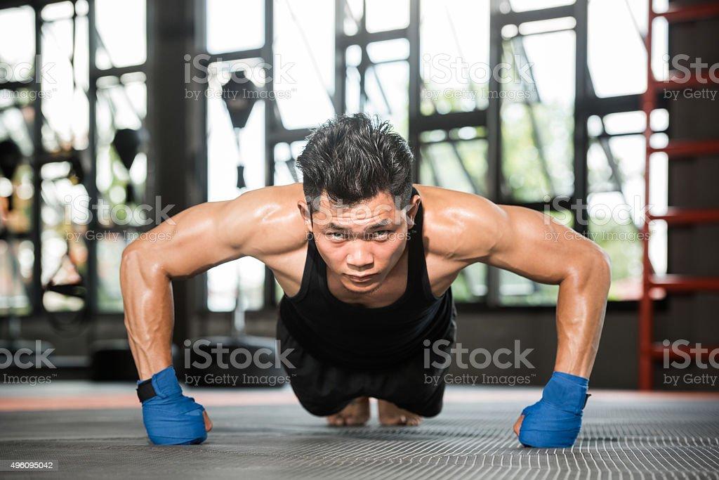 Attractive muscular man doing push-ups on gym floor stock photo