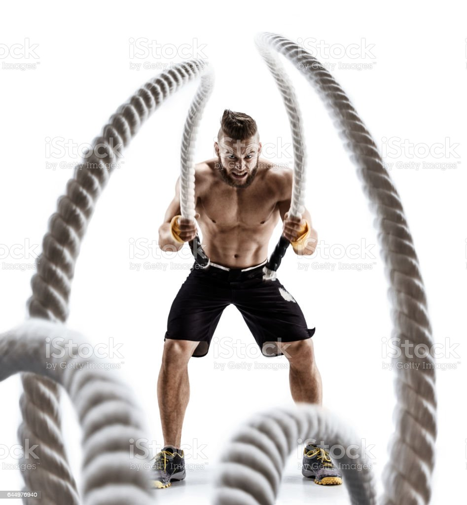 Attractive muscular man working out with heavy ropes. stock photo
