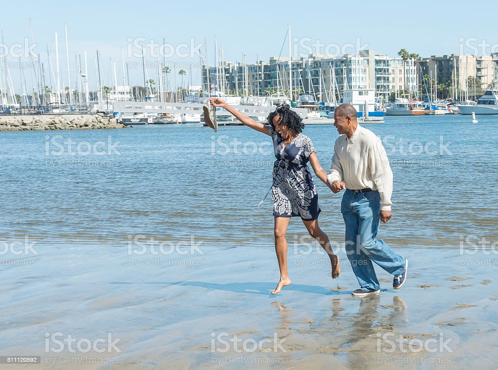 Attractive older African American Couple Running on beach stock photo
