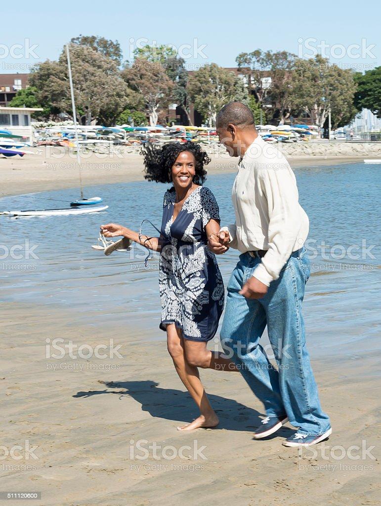Attractive older Couple Running on beach stock photo
