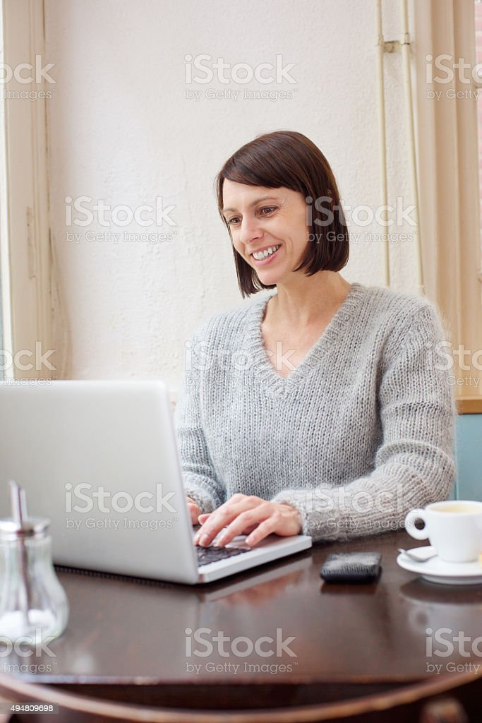 Attractive older woman smiling with laptop at home stock photo