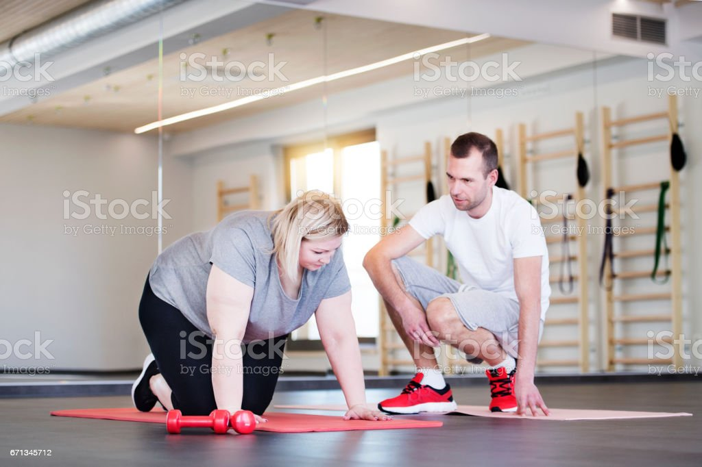 Attractive overweight woman with her personal trainer in modern gym working out on mat stock photo
