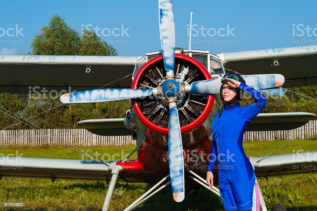 attractive pilot in helmet standing with airplane stock photo