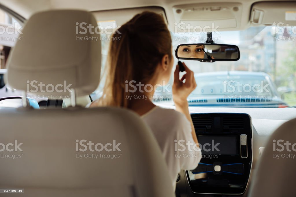 Attractive pretty woman looking into the rear view mirror stock photo