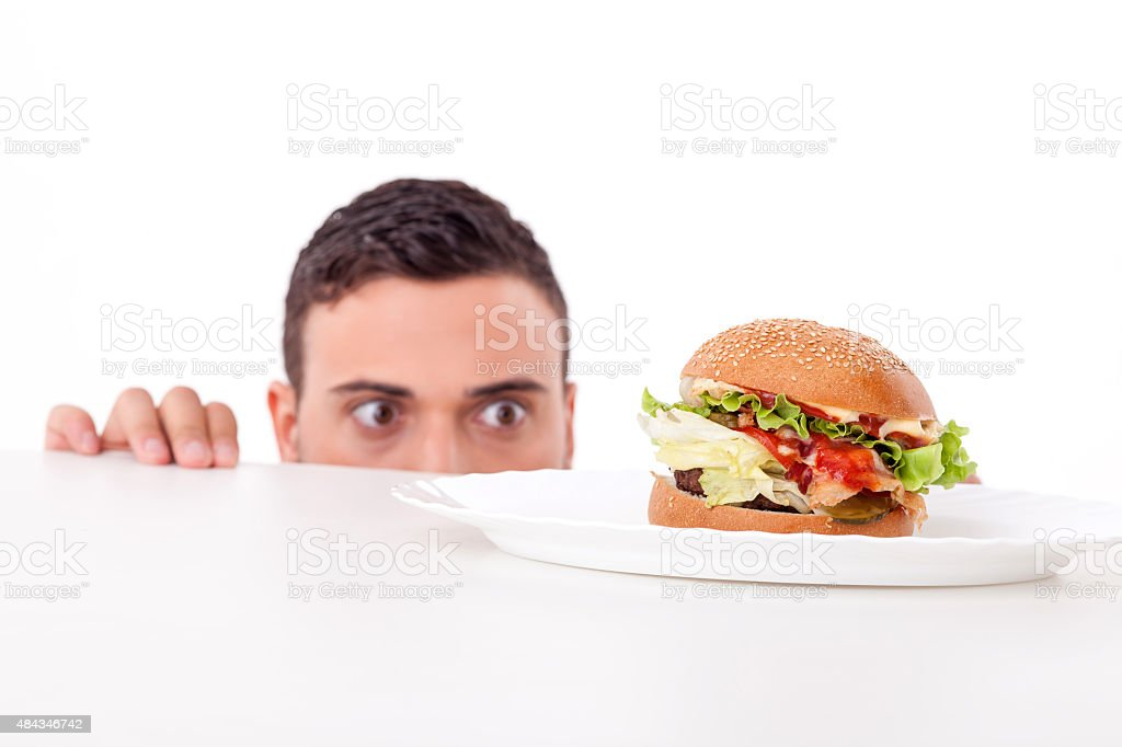 Attractive pretty young man is very hungry stock photo