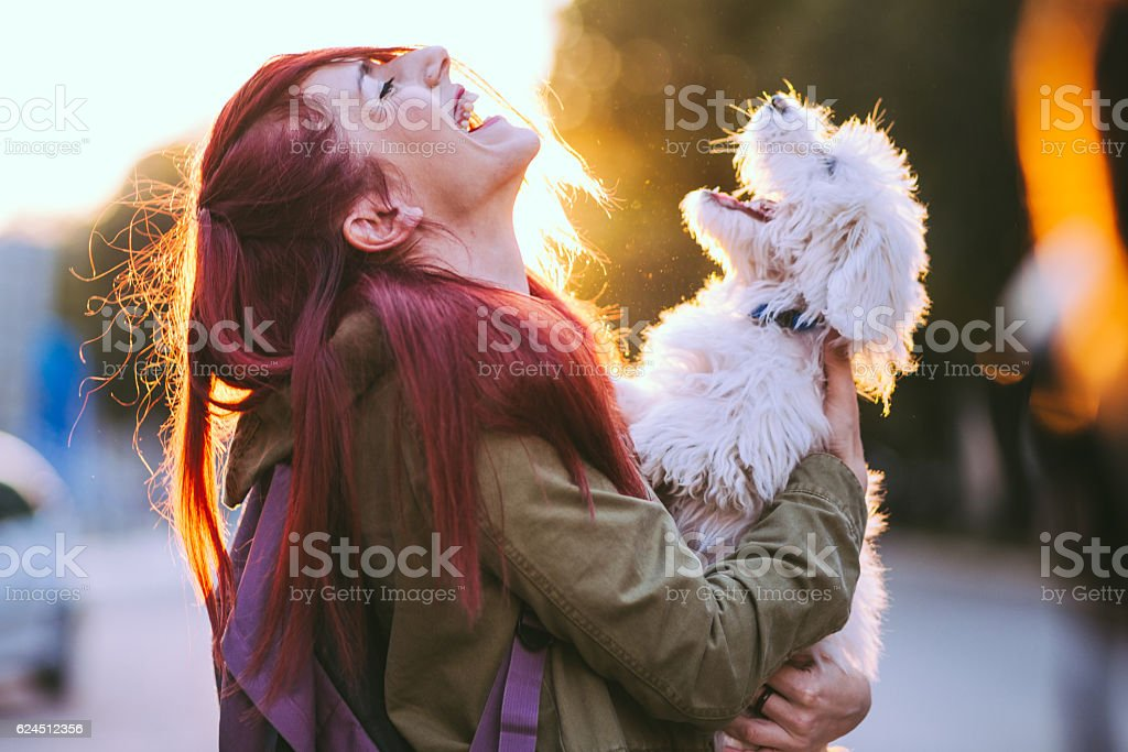 Attractive Redheaded Girl and White Puppy Smiling Together stock photo