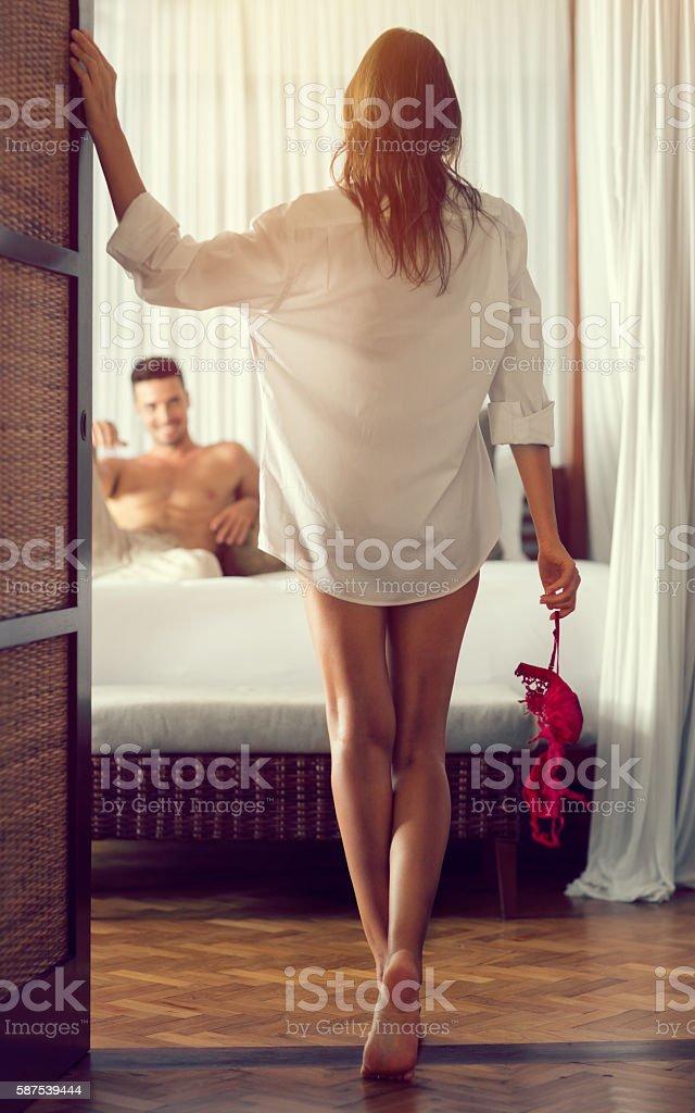 Attractive seductive woman at the bedroom door stock photo