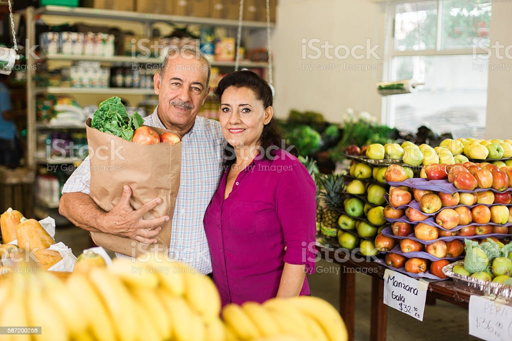 Attractive senior couple carrying groceries stock photo