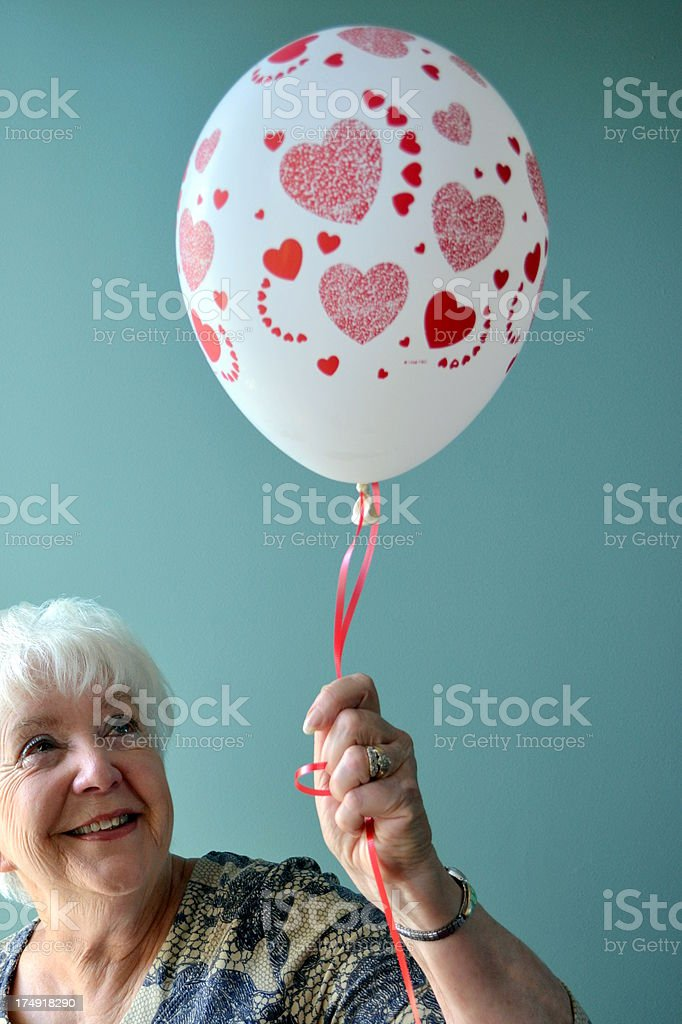 Attractive senior woman holding balloon with red hearts royalty-free stock photo