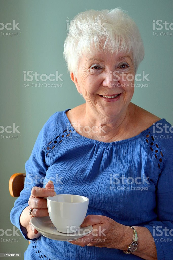 Attractive Senior woman just finishing cup of tea royalty-free stock photo