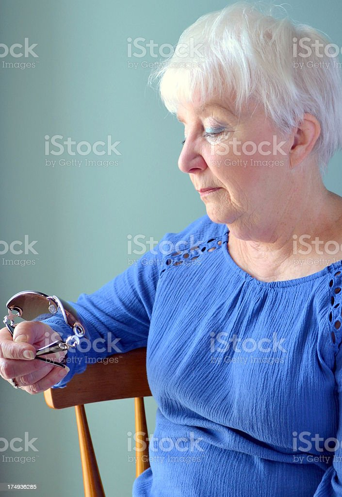 Attractive Senior woman pensively looking at sunglasses royalty-free stock photo