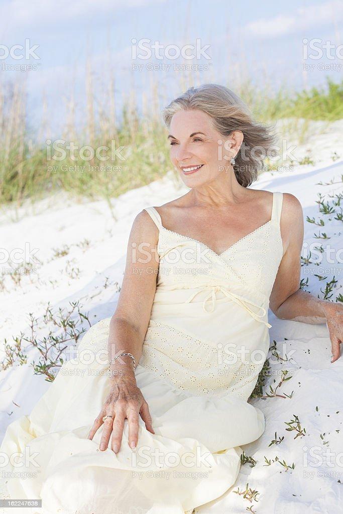 Attractive Senior Woman Sitting At Beach royalty-free stock photo