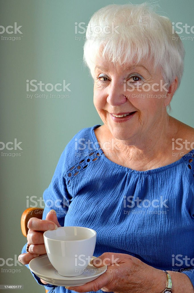 Attractive Senior woman smiling, just finishing cup of tea royalty-free stock photo