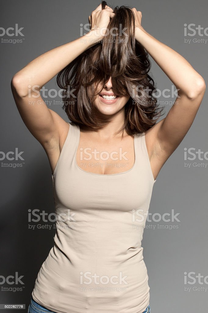 attractive shy sexy model posing in studio wearing beige shirt stock photo