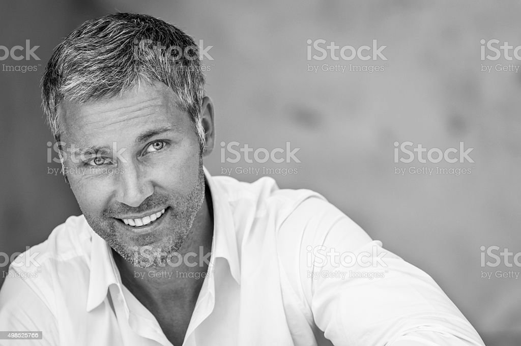 attractive smiling man looking up stock photo