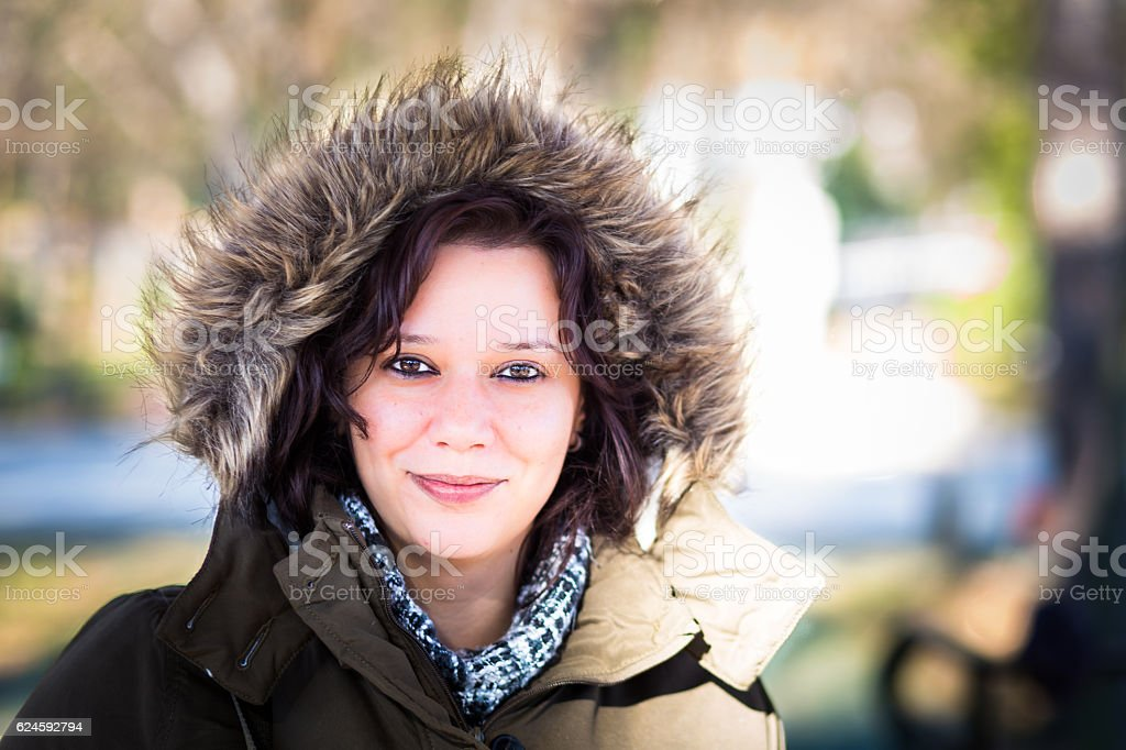 Attractive smiling winter girl outdoors with faux fur hood up stock photo