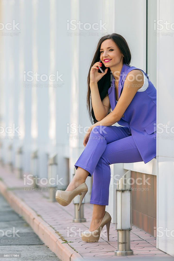 Attractive smiling woman sitting at wall niche talking on phone stock photo