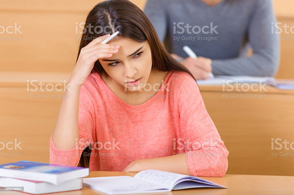 Attractive student girl looks concerned stock photo