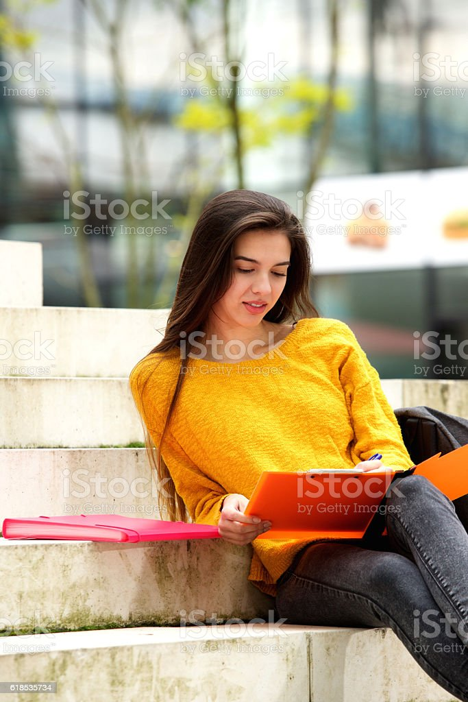 Attractive student sitting on steps studying stock photo