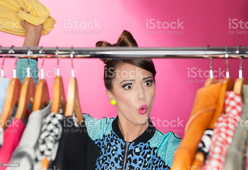 attractive surprised woman searching for clothing in a closet stock photo