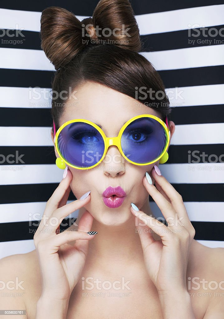 Attractive surprised young woman wearing sunglasses on striped background stock photo