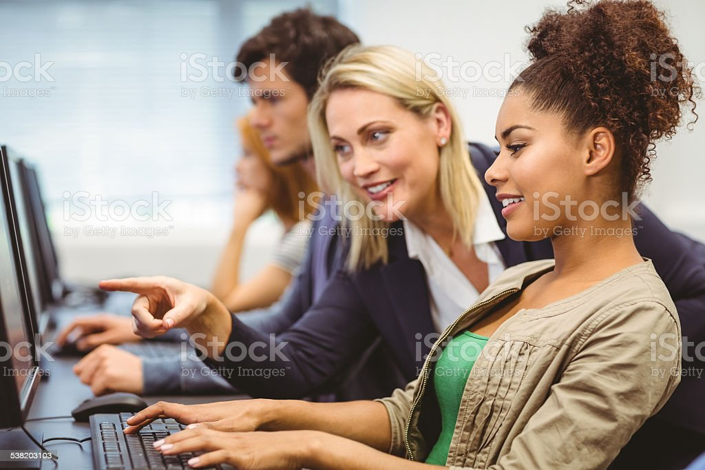 Attractive teacher talking to her student in computer class stock photo