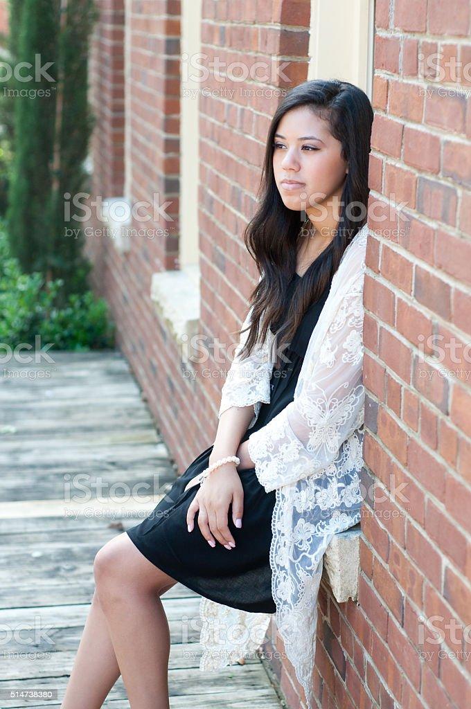 Attractive teen girl in window seal stock photo