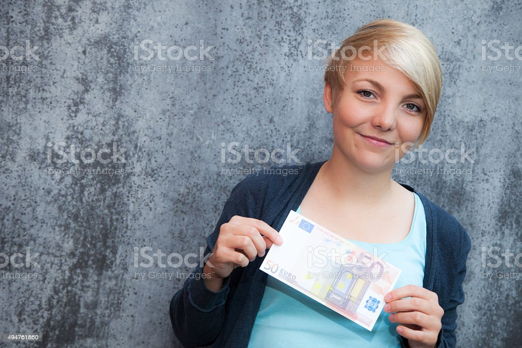 Attractive teenage girl holding fifty euro note stock photo
