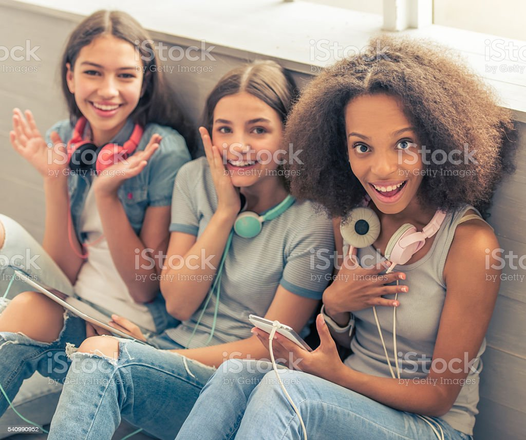 Attractive teenage girls with gadgets stock photo