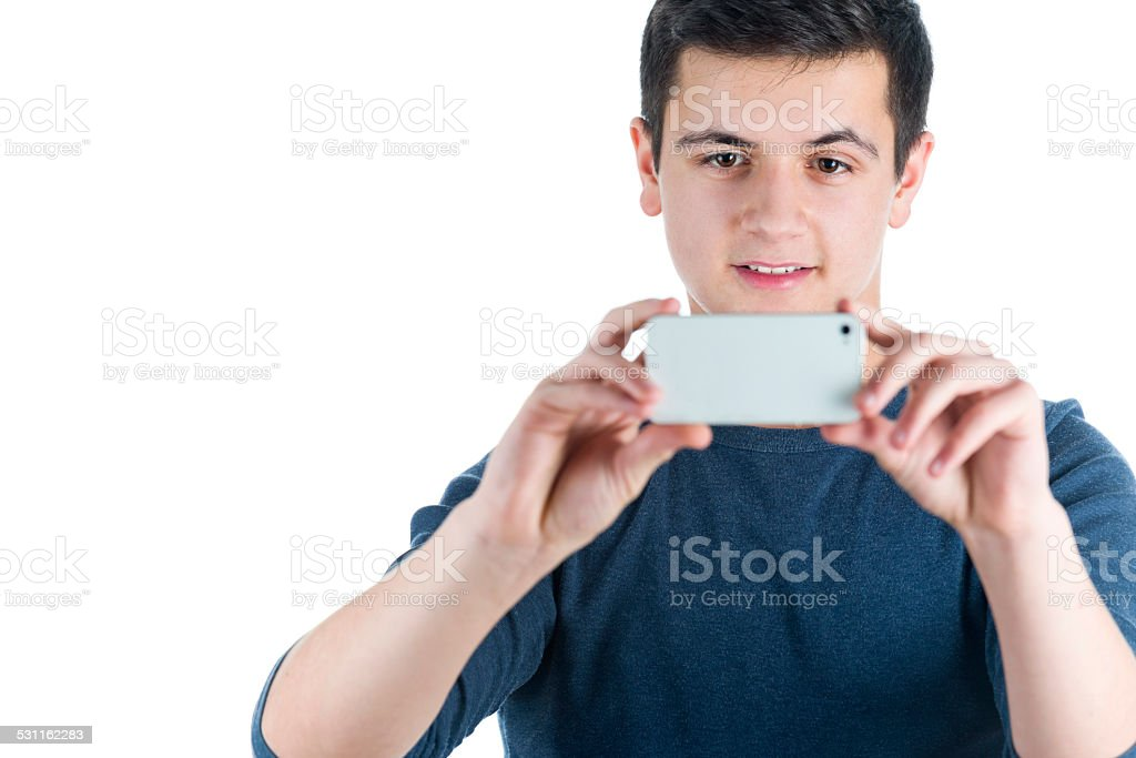 Attractive teenager boy taking pictures with his smartphone stock photo