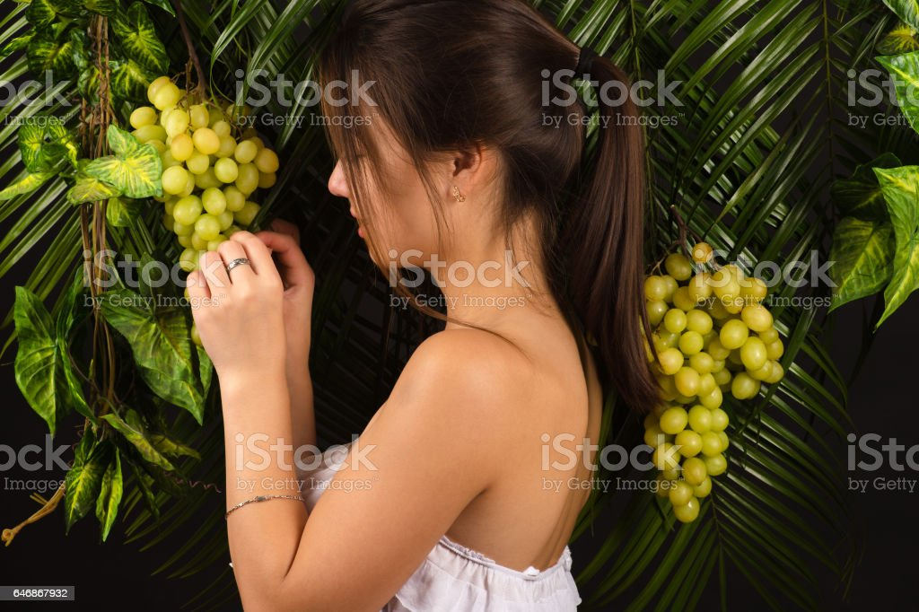 attractive teenager girl holding grapes stock photo