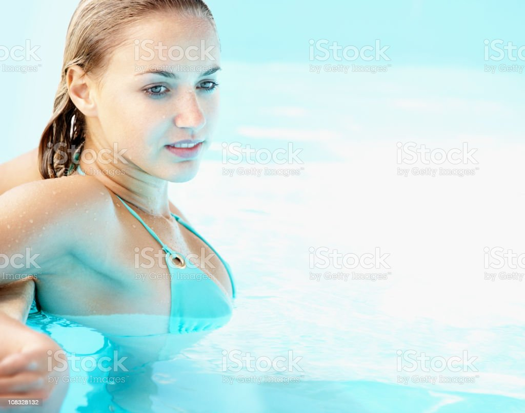 Attractive thoughtful female in a swimming pool stock photo