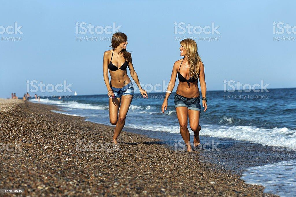Deux séduisantes jeunes fille amis courir au bord de mer. photo libre de droits
