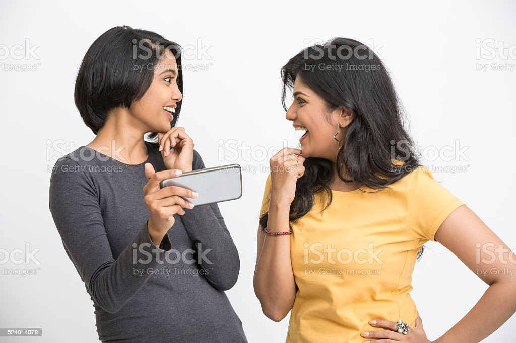 Attractive two young girls using smart phone stock photo