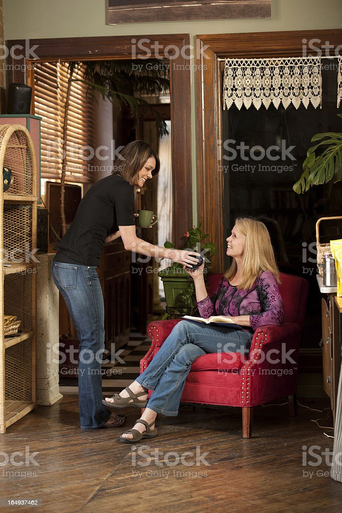 Attractive waitress serves customer in eclectic coffee house royalty-free stock photo