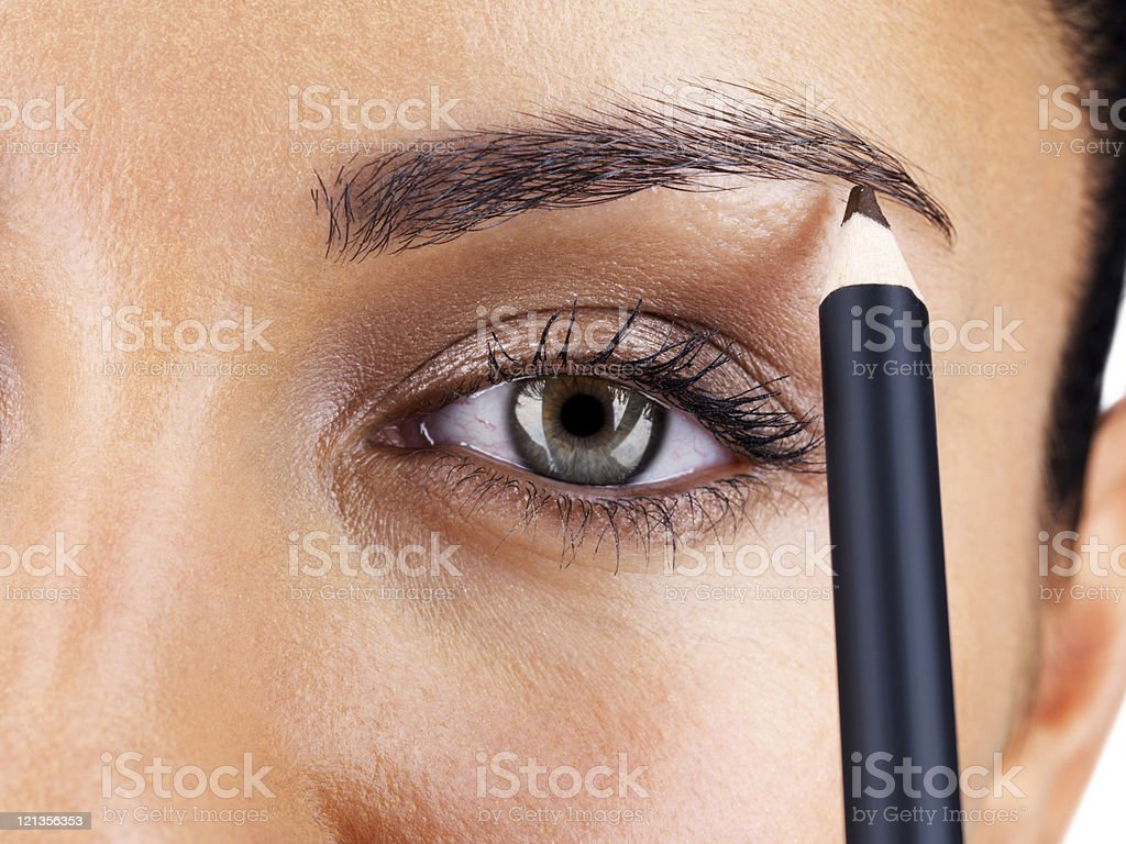 Attractive woman applying eyebrow pencil stock photo