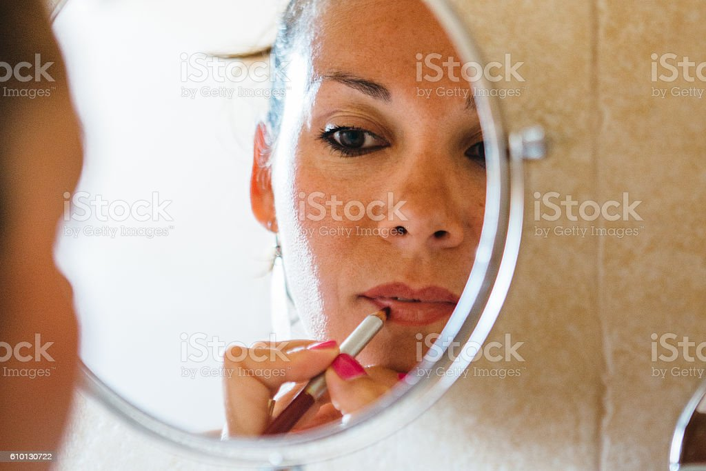 Attractive woman applying lip pencil stock photo