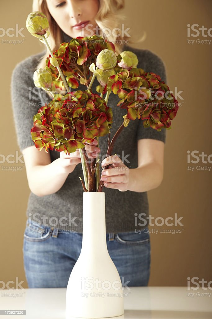 Attractive Woman Arranging Flowers in a Vase royalty-free stock photo
