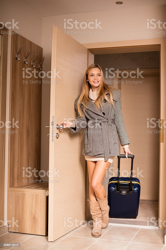 Attractive woman arrives in hotel room stock photo
