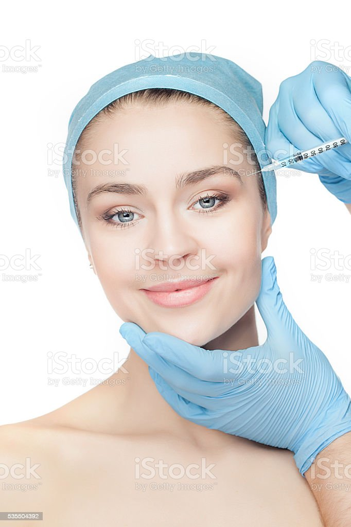 Attractive woman at plastic surgery with syringe in her face stock photo