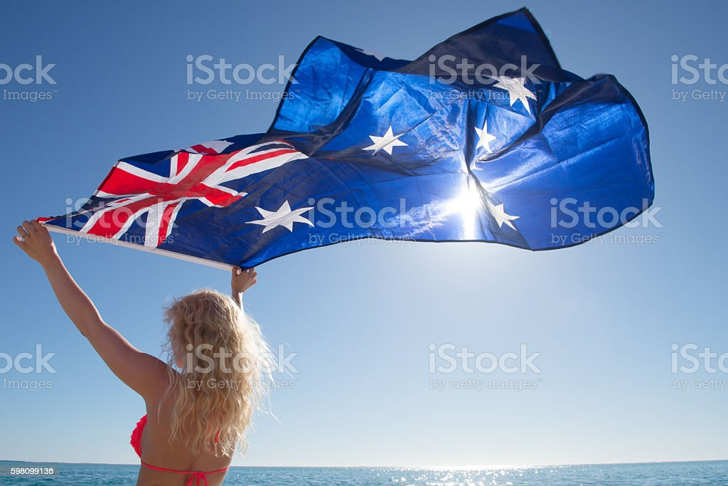 Attractive woman Australian flag at ocean stock photo