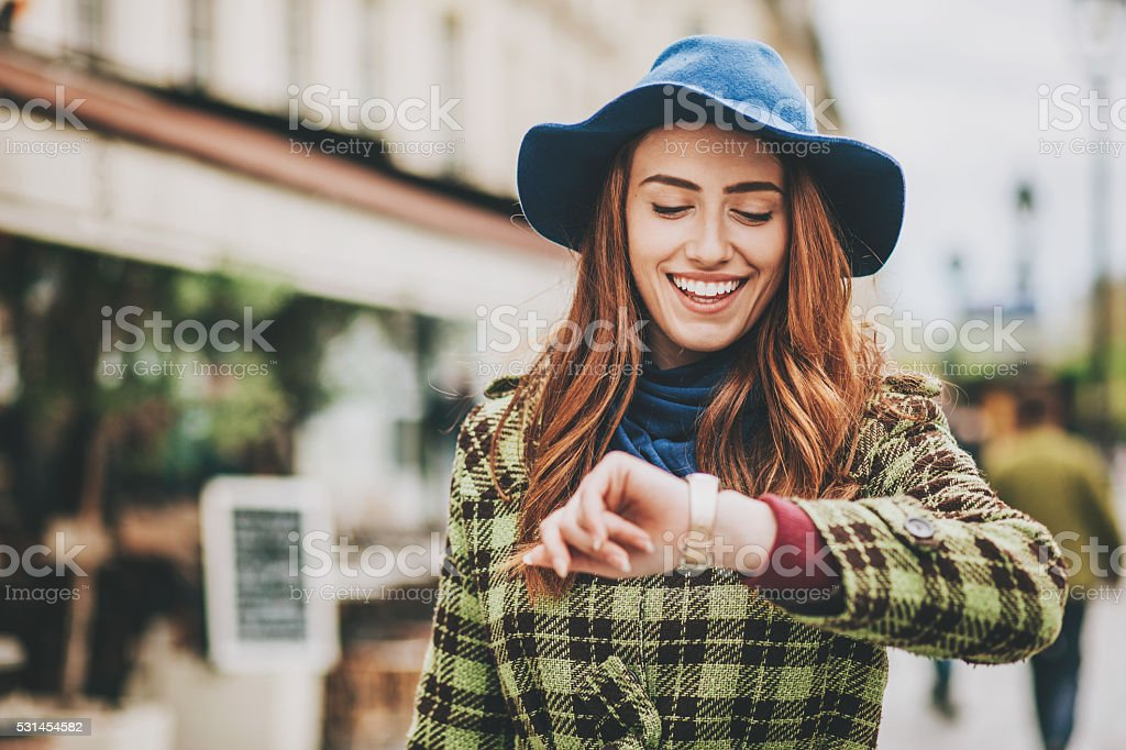 Attractive woman checking her watch on the street stock photo
